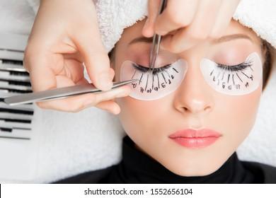 Eyelash extension procedure. Master tweezers fake long lashes beautiful female eyes.