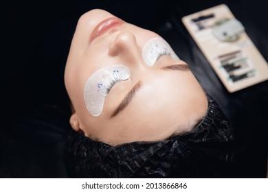 Eyelash extension procedure in salon. Master tweezers fake 2d lashes beautiful female eyes.