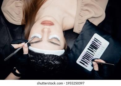 Eyelash extension procedure top view. Master tweezers fake 2d lashes beautiful female eyes.