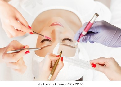 Eyelash Extension Procedure. Woman Eye with Long Eyelashes. Beautiful young girl  tweezing her eyebrows in a beauty salon. Eyebrow Correction. Beauty Concept. Permanent Makeup. Microblading brow.