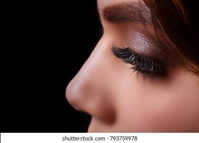 Eyelash Extension Procedure. Woman Eye with Long Eyelashes after Extension Procedure. White eyelashes. Dark background. Makeup. Close up, selective focus.