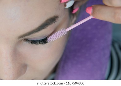 Eyelash extension procedure. Young beautiful woman eye with long false eyelashes. Close up macro shot of fashion eyes in beauty salon.