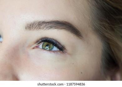 Eyelash extension procedure. Young beautiful woman eye with long false eyelashes. Close up macro shot of fashion eyes in beauty salon.