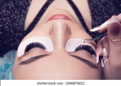 Eyelash extension process. Closeup portrait of young girl, woman with long and thick eyelashes, eyes closed and hand of a cosmetologist adding more eyelashes to her.