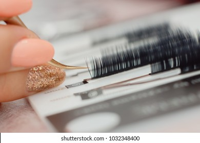 Eyelashes. Close-up tool for eyelash extension. Master of tweezers is working.