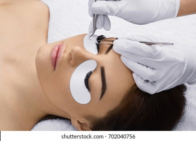 Eyelashes extensions. Fake Eyelashes. Eyelash Extension Procedure. Professional stylist lengthening female lashes. Master and a client in a beauty salon.