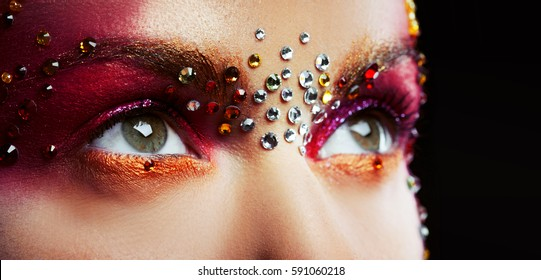 Eyes of a beautiful young woman in a bright designer makeup with rhinestones, body painting.