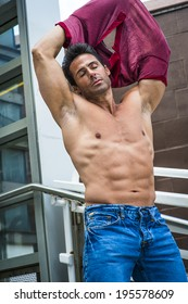 Eyes closed, arms raised, a handsome, sexy, middle age man is taking off his shirt, showing his strong body.