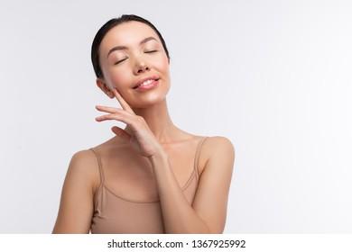 Eyes closed. Dark-haired woman wearing beige camisole closing her eyes feeling truly satisfied