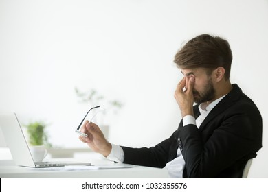 Eyes fatigue at work, tired exhausted businessman suffering from computer vision syndrome taking off glasses massaging eyes after long laptop use, overworked man feeling eye strain tension problem