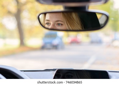Eyes of a female driver reflected in the rear view mirror inside a car with a view through the blurred windscreen and copy space