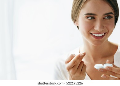 Eyes Health. Portrait Of Young Beautiful Woman With Natural Makeup And Contact Eye lens In Hand. Closeup Of Female Model Holding White Lens Box. Eye Care And Healthy Lifestyle. High Resolution Image.