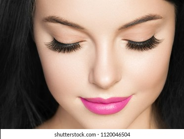 Eyes lashes extensions closed eyes woman with black hair and pink listick closeup face