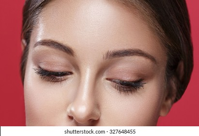 Eyes looking down Young beautiful woman face portrait with healthy skin on red background