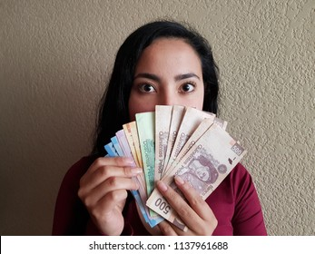 eyes on the face of a surprised woman and grabbing mexican banknotes