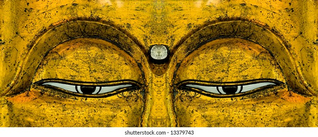 The eyes on a golden carving of Buddha's face.
