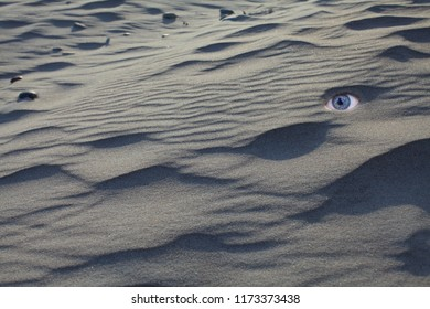 eyes on sand with shadows