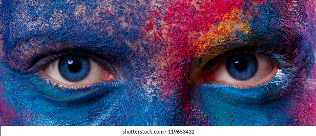 Eyes of woman with unusual paint make-up on black background