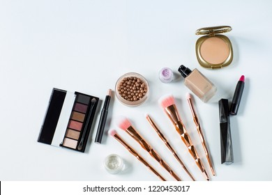 eyeshadow, nail polish, concealer, mascara, lipstick, powder and makeup brushes on a white background