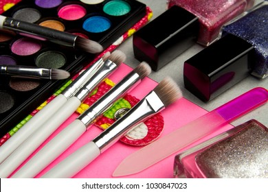 Eyeshadow palette and nail Polish in pink and silver geometric background. Decorative cosmetics for professional makeup. Eyeshadow and nail Polish colors trend.