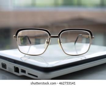 Eyesight glasses on a white laptop near window glass