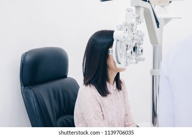 eyesight measurement to a young woman with a optical phoropter.