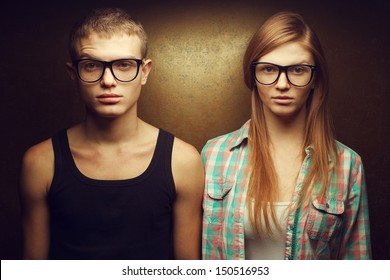 Eyewear concept. Funny portrait of gorgeous red-haired (ginger) fashion twins in casual shirts wearing trendy glasses and posing over golden background. Hipster style. Close up. Studio shot
