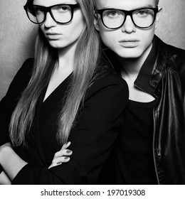Eyewear concept. Portrait of gorgeous fashion twins in black clothes wearing trendy glasses and posing over metal background together. Perfect hair and skin. Natural make-up. Studio shot