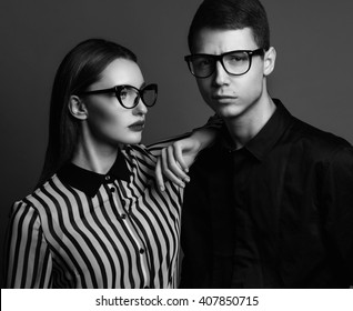 Eyewear concept. Portrait of gorgeous fashion couple in black clothes wearing trendy glasses and posing over gray background together. Perfect skin. Vogue style. Close up. Studio shot
