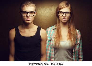 Eyewear concept. Portrait of gorgeous red-haired (ginger) fashion twins in casual shirts wearing trendy glasses and posing over golden background together. Hipster style. Studio shot
