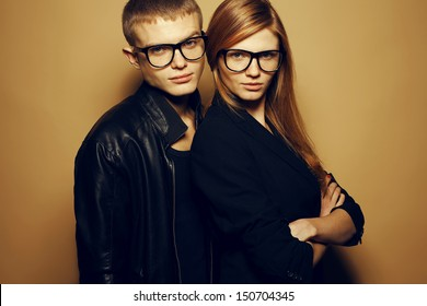 Eyewear concept. Portrait of gorgeous red-haired fashion twins in black clothes wearing trendy glasses and posing over beige background together. Perfect hair & skin. Natural make-up. Studio shot