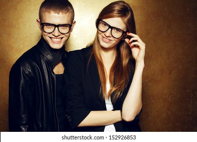 Eyewear concept. Portrait of gorgeous red-haired twins in black clothes wearing trendy glasses & posing over golden background together & smiling. Natural make-up. Copy-space