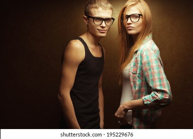 Eyewear concept. Portrait of smiling gorgeous red-haired (ginger) fashion twins in casual shirts wearing trendy glasses and posing over golden background. Hipster style. Copy-space. Studio shot