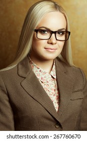 Eyewear concept. Portrait of young beautiful business woman wearing trendy glasses, casual shirt, jacket and posing over golden background. Close up. Studio shot