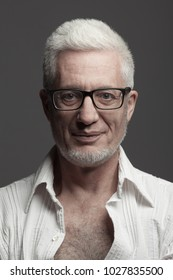 Eyewear, Fabulous at any age concept. Portrait of 60-year-old man standing over gray background looking at camera. Close up. Studio shot