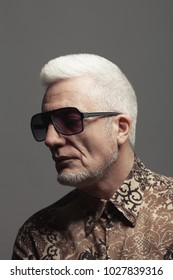 Eyewear, Fabulous at any age concept. Portrait of 60-year-old man standing over gray background wearing ultra modern shirt. Fashionista style. Close up. Text space. Studio shot