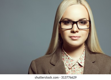 Eyewear fashion concept. Portrait of young beautiful blonde girl wearing trendy glasses, casual shirt, jacket and posing over gray background. Close up. Copy-space. Studio shot