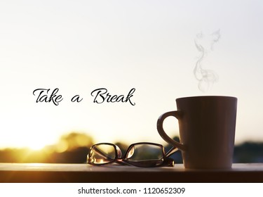 "A eyewear glasses and mug with sunset background. Wording "" Take a Break""."