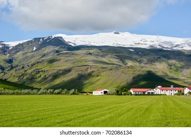 Eyjafjallajokull volcano in Iceland against blue summer sky with clouds. Farm Thorvaldseyri visible.