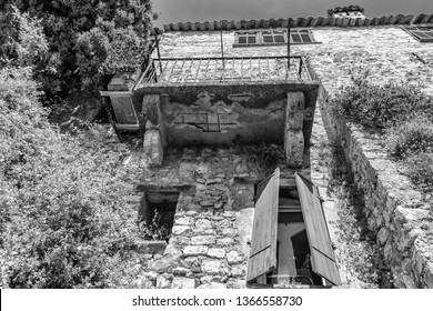 Eze, France, September 5, 2018:  Black and white photo of the facade of an old house in a narrow street in the old center of the  picturesque medieval village of Eze