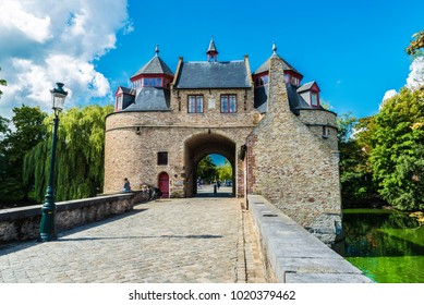 Ezelpoort (Donkey's gate), fortified gate on the river with people around, in the medieval city of Bruges, Belgium
