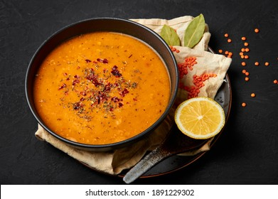 Ezogelin Soup in black bowl on dark slate table top. Turkish cuisine traditional dish with red lentils, bulgur and rice