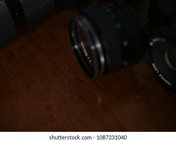 F 50 mm tokina and yashica photography vintage camera lens against brown background with other lenses visible in the background