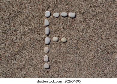 F letter made of stones on sand