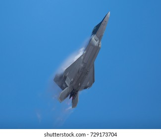 F-22 Raptor in a high-G maneuver, with afterburners on, and condensation clouds and streaks around the plane.