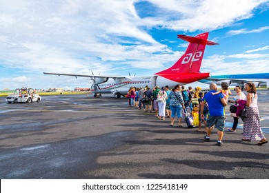 """Faaa, French Polynesia - Nov 06 2017. Happy tourists boarding Air Tahiti ATR 72 """"Tapuata"""" on their way from Papeete to their remote island exciting destination somewhere around Tahiti and her islands."""