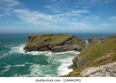 Fabled site of King Arthurs castle Camelot at Tintagel on the North Cornish coast. Looking along the coast on a clear summers day with waves breaking below.