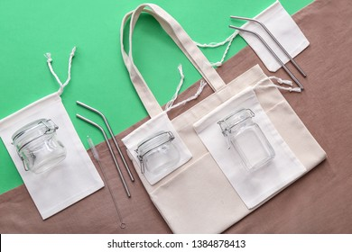 Fabric bags, glass jars and metal straws on color background. Zero waste concept