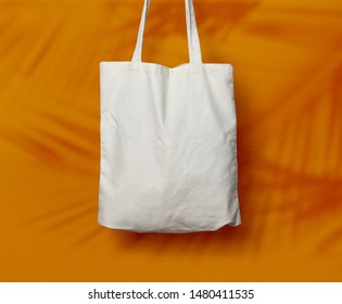 Fabric Canvas Tote Bag or Goodie Bag Isolated with Palm Leaf Shadow on Yellow/Orange Wall Background