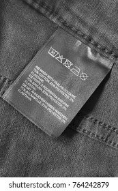 Fabric composition and washing instructions clothes label on black denim background